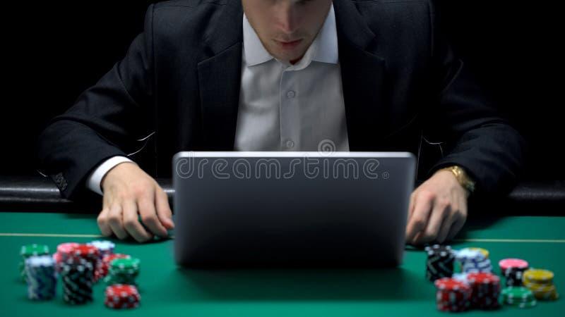 Hombre de negocios adicto de juego delante del ordenador portátil, apuesta perdidosa del deporte, arruinada imagen de archivo libre de regalías
