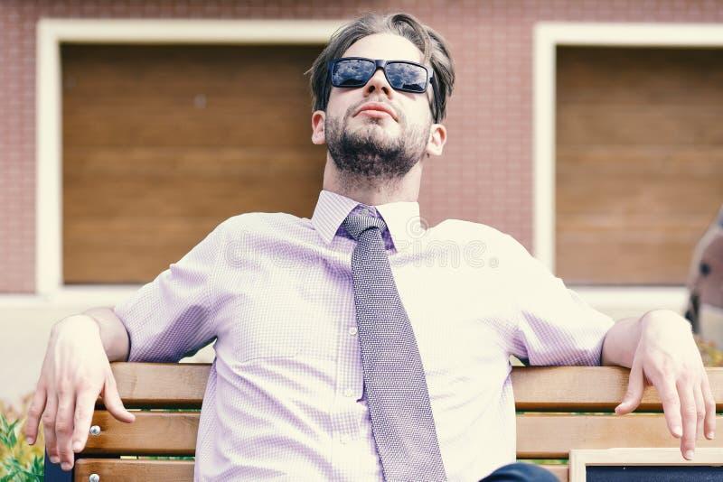 Hombre de negocios adulto que mira las gafas de sol para arriba que llevan en la calle de la ciudad foto de archivo libre de regalías