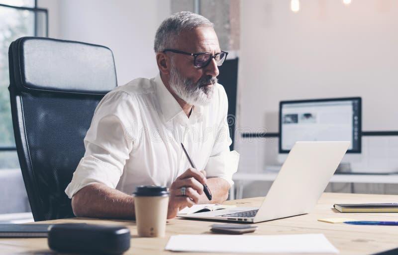 Hombre de negocios adulto que trabaja en el ordenador portátil móvil mientras que se sienta en la tabla de madera en el lugar mod fotos de archivo libres de regalías