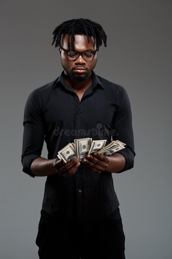 Hombre de negocios africano acertado joven que sostiene el dinero sobre fondo oscuro fotos de archivo