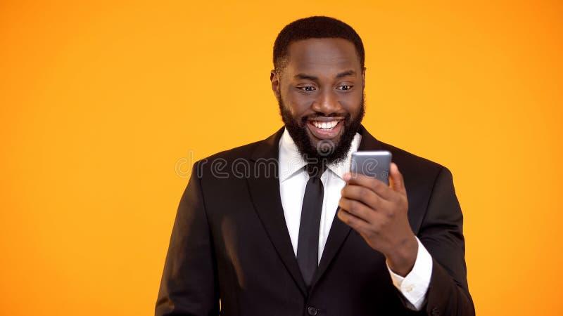 Hombre de negocios africano alegre que sostiene smartphone y que sonr?e, app de reservaci?n en l?nea fotos de archivo