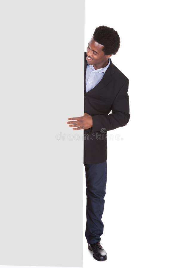 Hombre de negocios africano con el cartel foto de archivo
