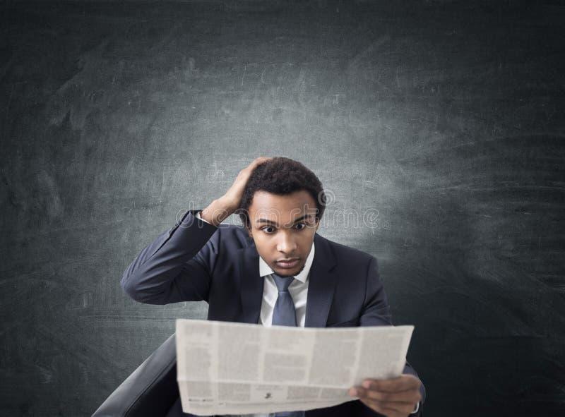 Hombre de negocios africano con el periódico, pizarra imagenes de archivo