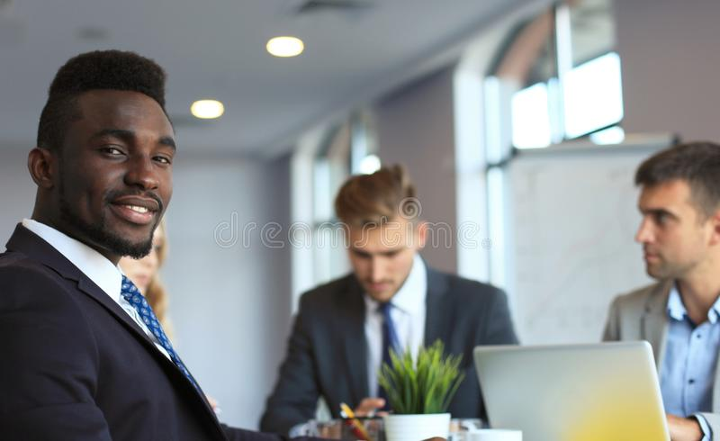 Hombre de negocios africano confiado sonriente en una reunión con colegas asentados en una mesa de reuniones en la oficina fotos de archivo libres de regalías