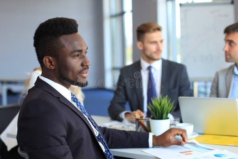 Hombre de negocios africano confiado sonriente en una reunión con colegas asentados en una mesa de reuniones en la oficina imagenes de archivo