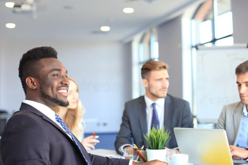Hombre de negocios africano confiado sonriente en una reunión con colegas asentados en una mesa de reuniones en la oficina imagen de archivo libre de regalías