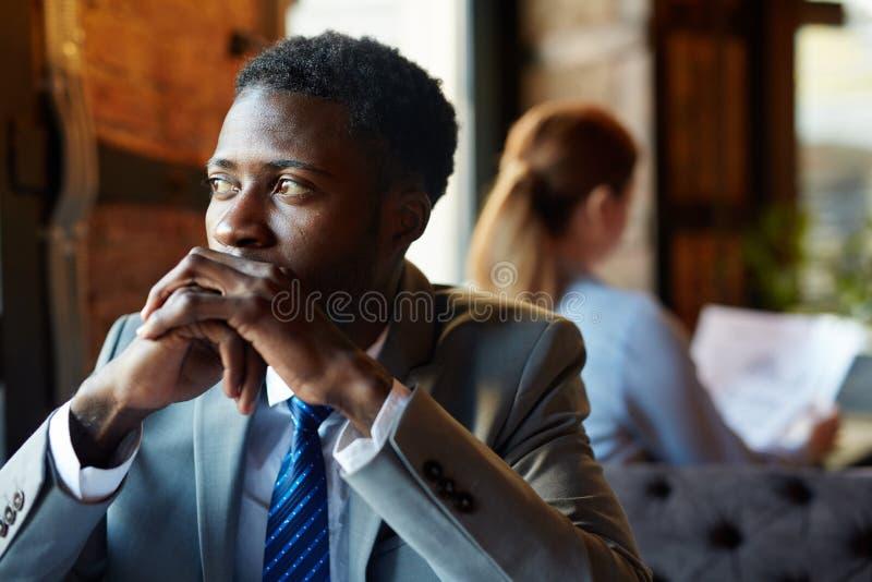 Hombre de negocios africano de pensamiento en café foto de archivo libre de regalías