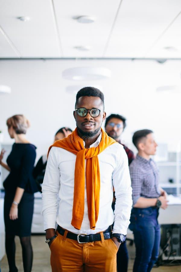 Hombre de negocios africano elegante que sonríe en la cámara con los colegas diversos foto de archivo libre de regalías
