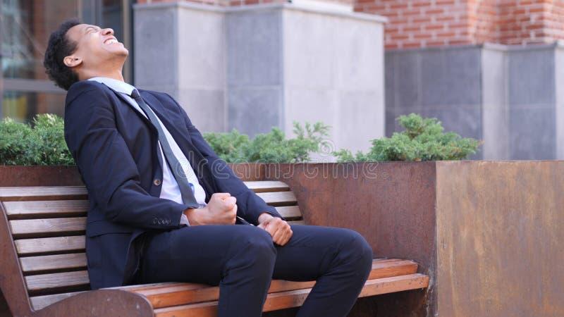 Hombre de negocios africano gritador enojado Reacting al problema en el trabajo imagenes de archivo