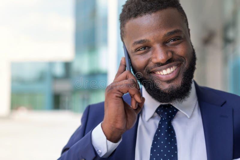 Hombre de negocios africano hermoso en el traje que habla en el teléfono al aire libre Copie el espacio imágenes de archivo libres de regalías