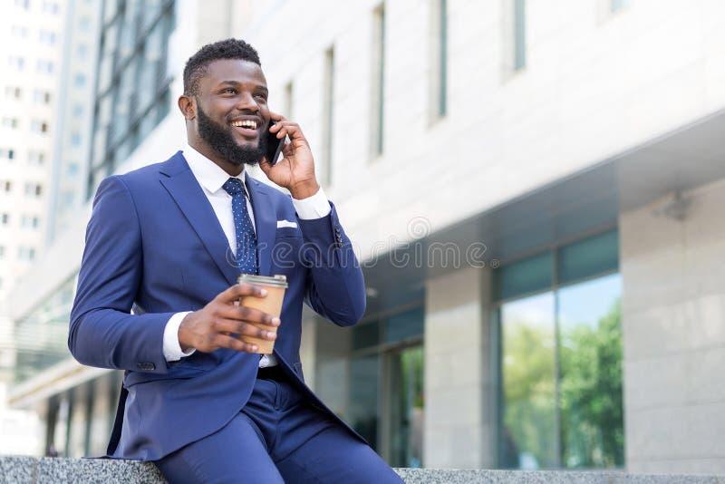 Hombre de negocios africano joven que habla en el teléfono con una taza de café mientras que sienta el exterior foto de archivo