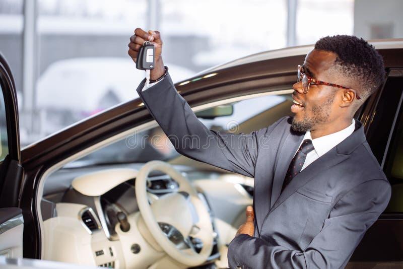 Hombre de negocios africano joven Sitting In un coche que muestra llave del coche foto de archivo