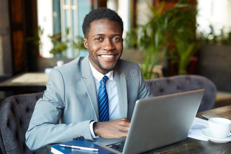 Hombre de negocios africano joven Working con el ordenador portátil imágenes de archivo libres de regalías