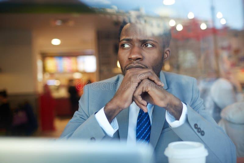 Hombre de negocios africano preocupante Working en cafetería imagen de archivo libre de regalías