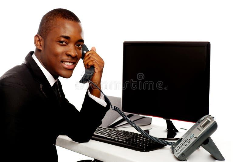 Hombre de negocios africano que atiende a llamada de teléfono foto de archivo libre de regalías