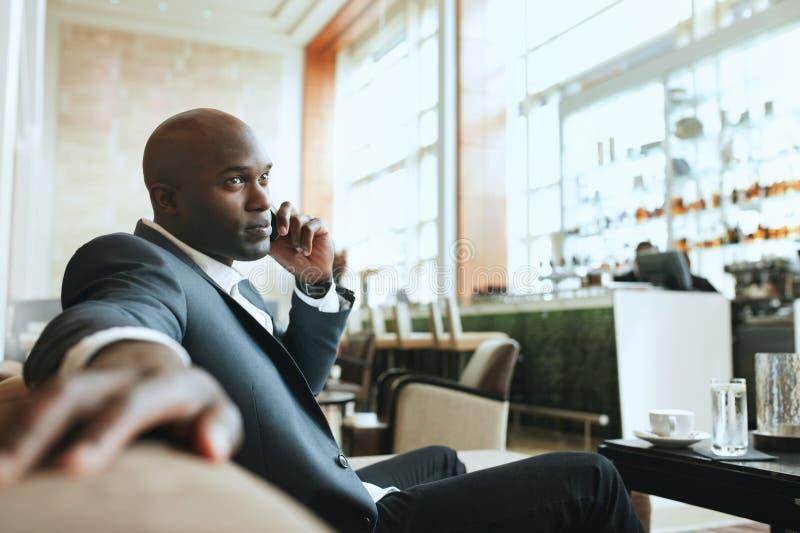 Hombre de negocios africano que espera en un pasillo del hotel imagenes de archivo