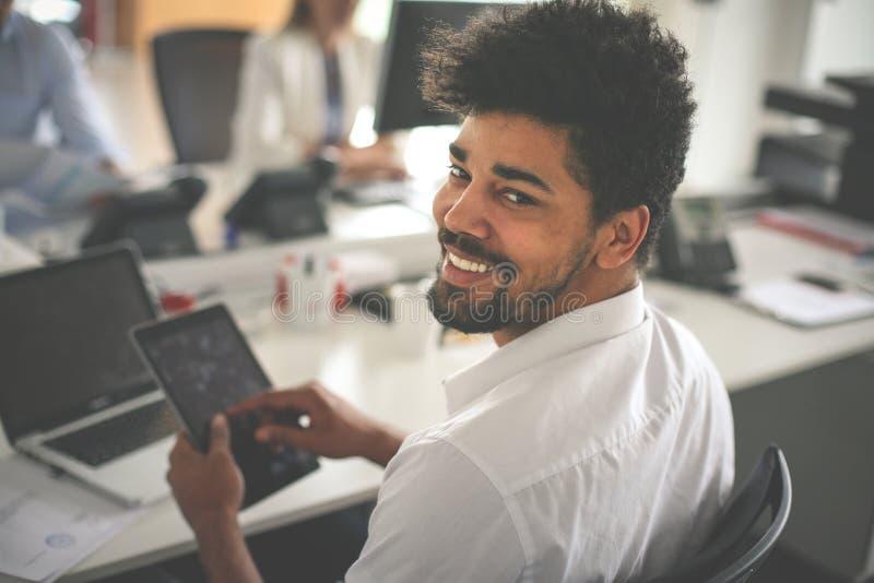 Hombre de negocios africano que mecanografía en la tableta digital imagenes de archivo