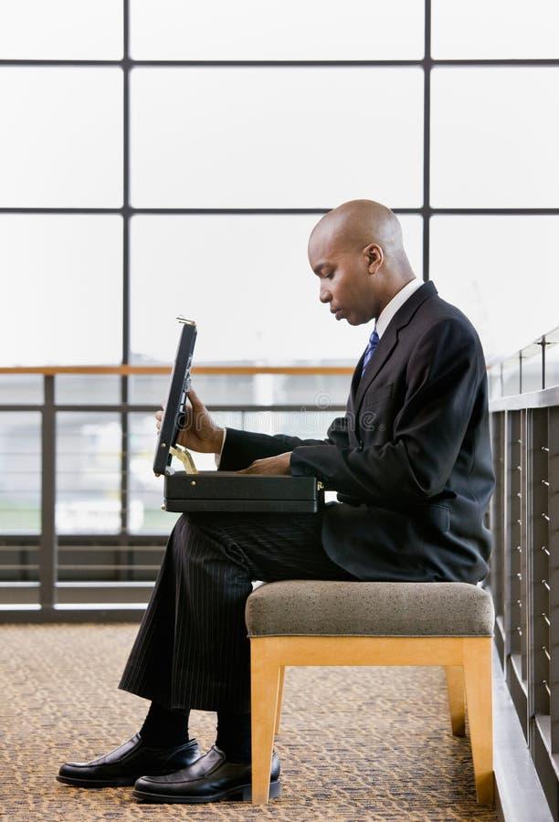 Hombre de negocios africano que mira en cartera imagen de archivo libre de regalías