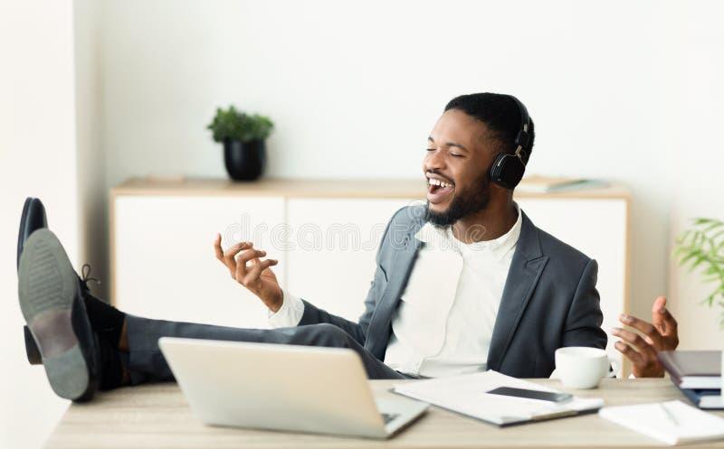 Hombre de negocios africano que se imagina que él es un rockstar imagenes de archivo