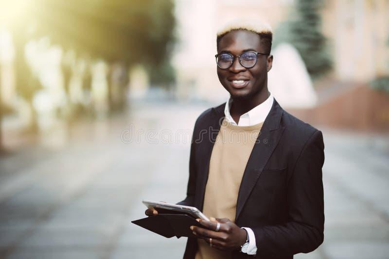Hombre de negocios africano que trabaja con la tableta al aire libre Personas negras - concepto sobre gente, negocio, forma de vi imagen de archivo