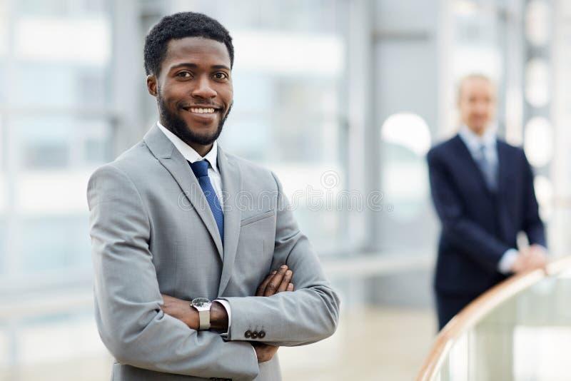 Hombre de negocios africano sonriente en el edificio de oficinas imagenes de archivo