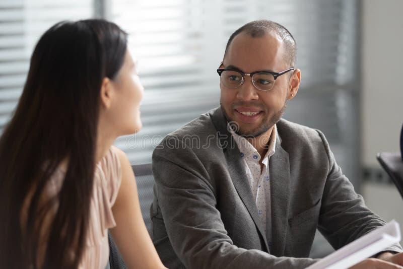 Hombre de negocios africano sonriente que habla con el colega asiático de la mujer en oficina imagen de archivo libre de regalías