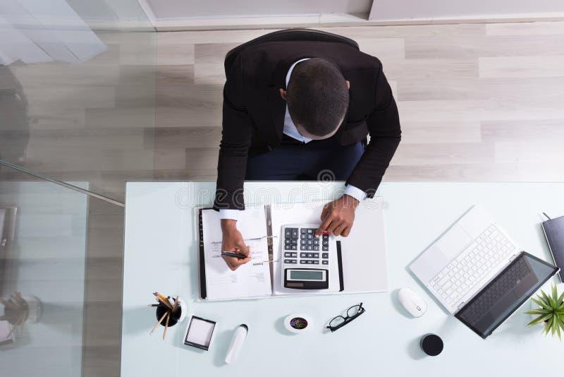 Hombre de negocios africano sonriente Working At Workplace fotografía de archivo libre de regalías