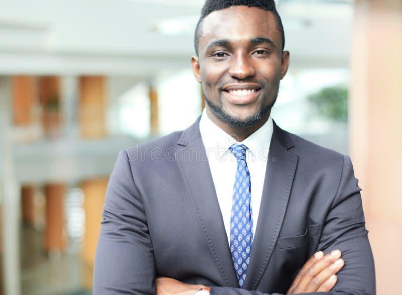 Hombre de negocios afroamericano acertado del hombre de negocios que se coloca en oficina fotos de archivo
