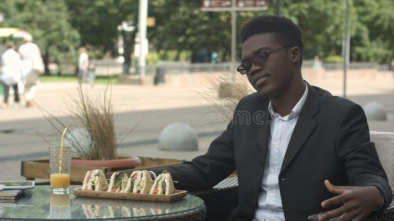 Hombre de negocios afroamericano cansado que se sienta en el café que parece agujereado o alimentado para arriba fotografía de archivo