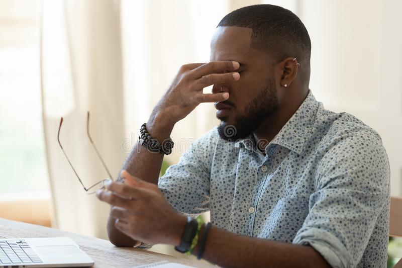 Hombre de negocios afroamericano cansado que sostiene los vidrios que sienten la fatiga visual fotografía de archivo