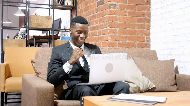 Hombre de negocios afroamericano Cheering Success, trabajando en el ordenador portátil fotos de archivo libres de regalías