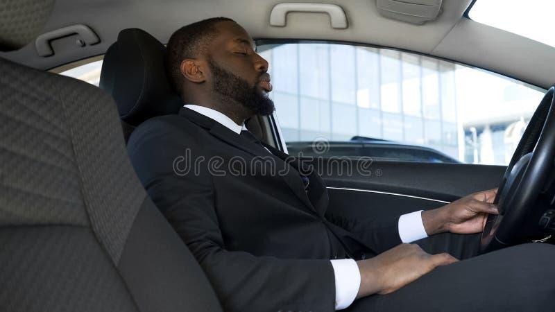 Hombre de negocios afroamericano con exceso de trabajo que se sienta en el coche, cansado después de día agotador imágenes de archivo libres de regalías