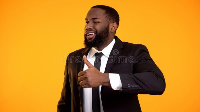 Hombre de negocios afroamericano confiado en el traje que hace los pulgares-para arriba y que gui?a, anuncio fotos de archivo