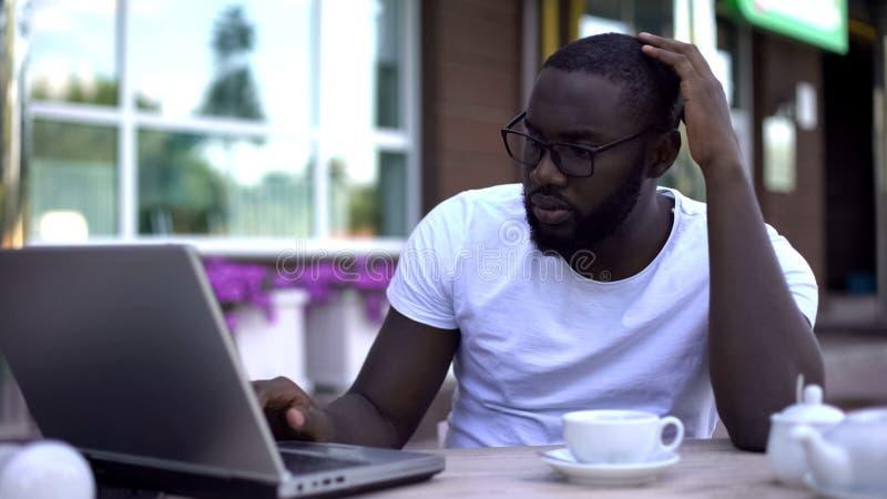 Hombre de negocios afroamericano confundido que trabaja en el ordenador portátil en el café, problemas del trabajo foto de archivo