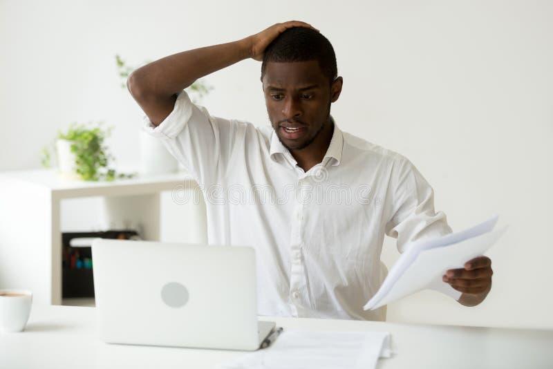 Hombre de negocios afroamericano confuso que tiene problema con el comput fotografía de archivo