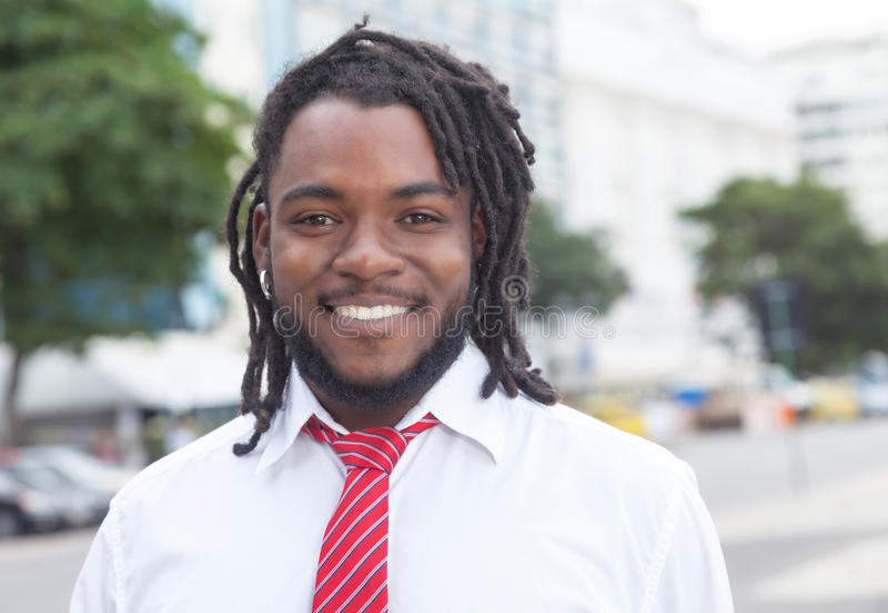 Hombre de negocios afroamericano de risa con los dreadlocks en la ciudad fotografía de archivo libre de regalías