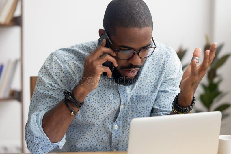 Hombre de negocios afroamericano enojado enojado que habla en el tel?fono m?vil en oficina fotos de archivo
