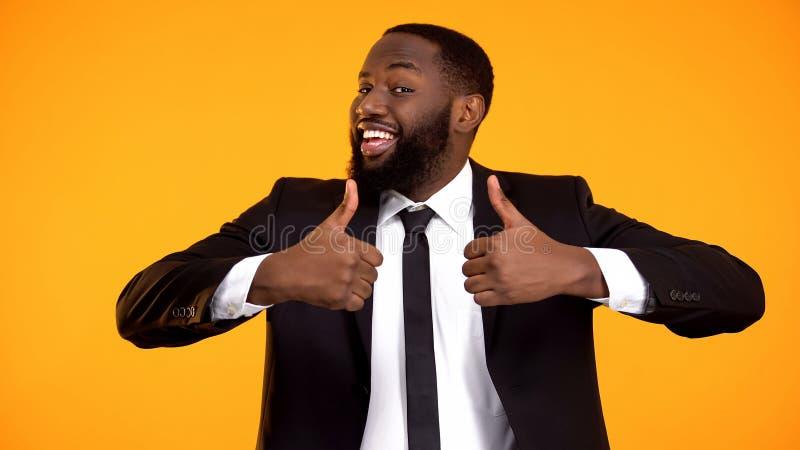 Hombre de negocios afroamericano feliz que hace los pulgares-para arriba dobles gesto, recomendaci?n foto de archivo
