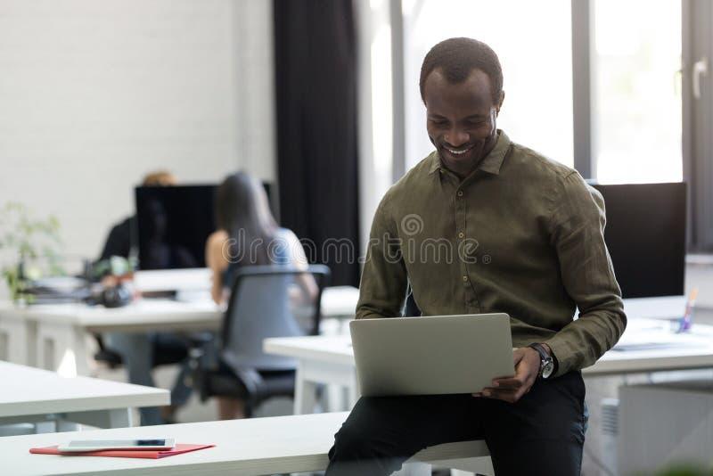 Hombre de negocios afroamericano feliz que se sienta en su escritorio y mecanografiar imagen de archivo libre de regalías
