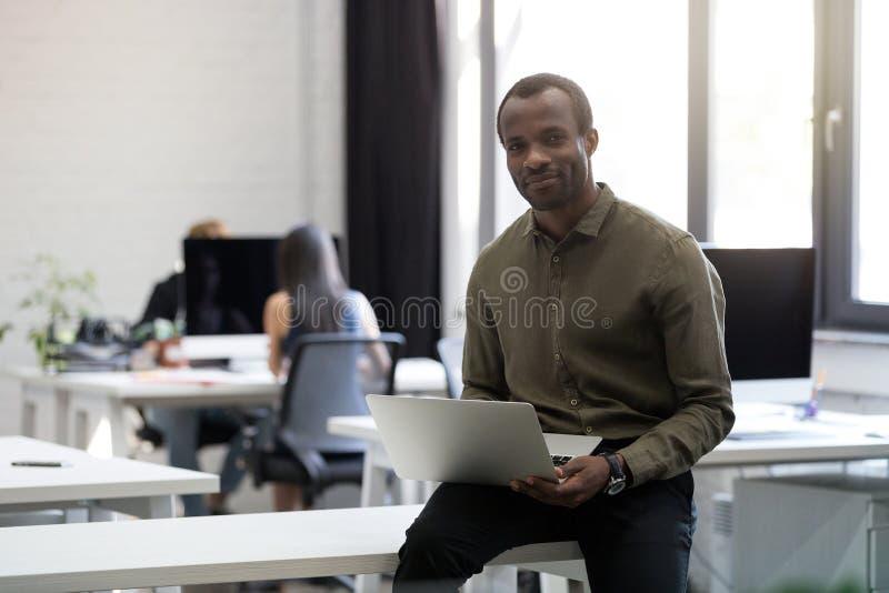 Hombre de negocios afroamericano feliz sonriente que se sienta en su escritorio imagen de archivo libre de regalías
