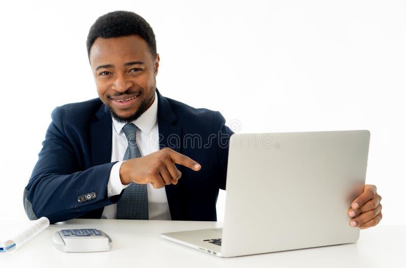 Hombre de negocios afroamericano hermoso feliz atractivo que trabaja en el ordenador portátil en el escritorio en la oficina foto de archivo