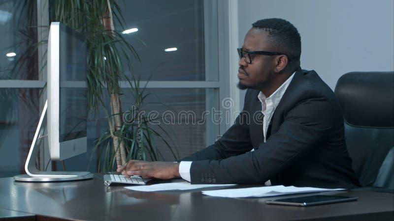 Hombre de negocios afroamericano hermoso que trabaja y que mecanografía en el ordenador portátil en la oficina imagen de archivo