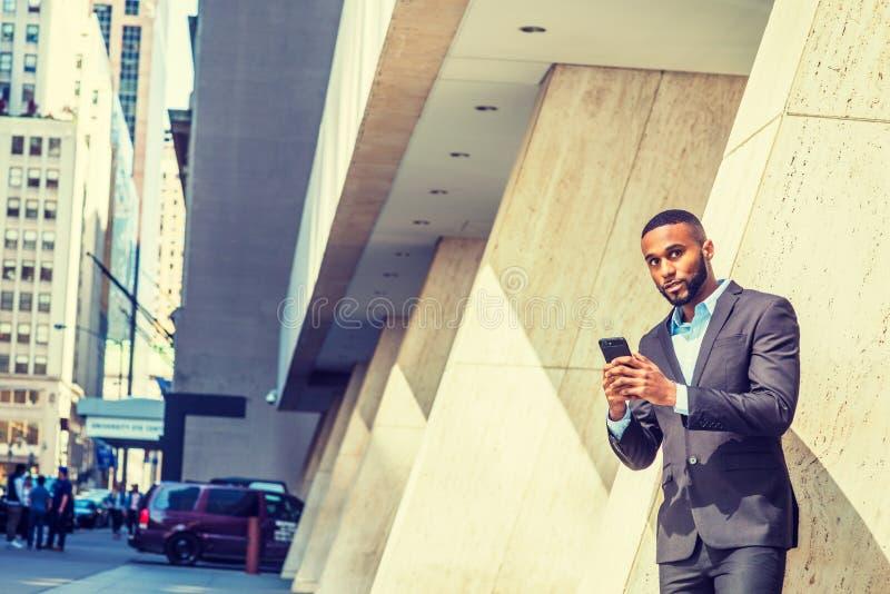 Hombre de negocios afroamericano joven con la barba, pelo corto, mandando un SMS en el teléfono celular afuera en New York City fotos de archivo