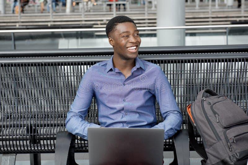 Hombre de negocios afroamericano joven feliz que se sienta en banco con el ordenador portátil fotos de archivo