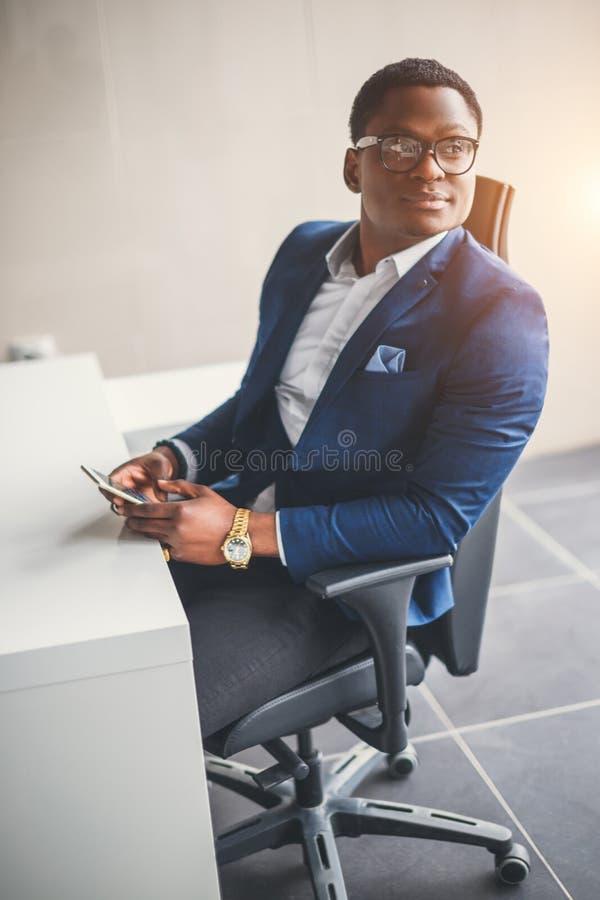 Hombre de negocios afroamericano pacífico en oficina moderna fotos de archivo