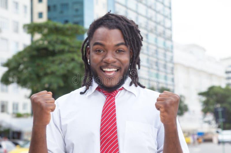 Hombre de negocios afroamericano que anima con los dreadlocks en la ciudad imagen de archivo