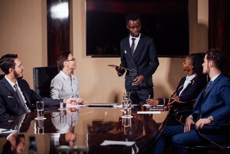 Hombre de negocios afroamericano que da la presentación a los socios fotografía de archivo