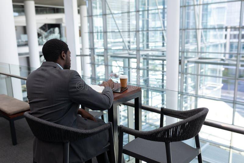 Hombre de negocios afroamericano que se sienta en la tabla y que escribe en el diario en oficina fotografía de archivo libre de regalías