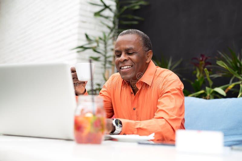 Hombre de negocios afroamericano que se sienta en una tabla del café imagen de archivo libre de regalías