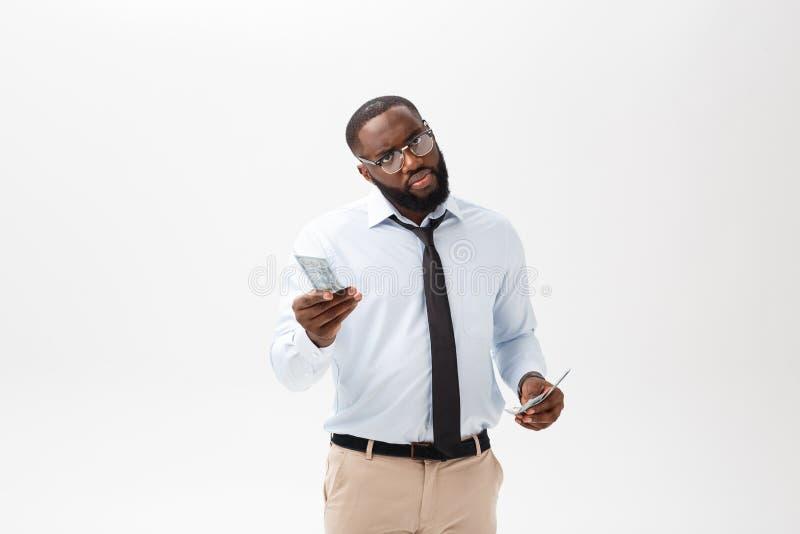 Hombre de negocios afroamericano que sostiene efectivo y en la cámara de mirada seria Interior, aislado en fondo gris foto de archivo libre de regalías